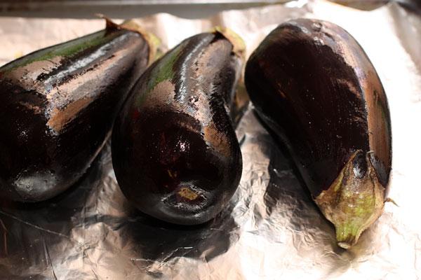 Разогрейте духовку до 200 градусов, вымытые и обсушенные баклажаны смажьте маслом и проколите в нескольких местах, чтобы они не лопнули.
