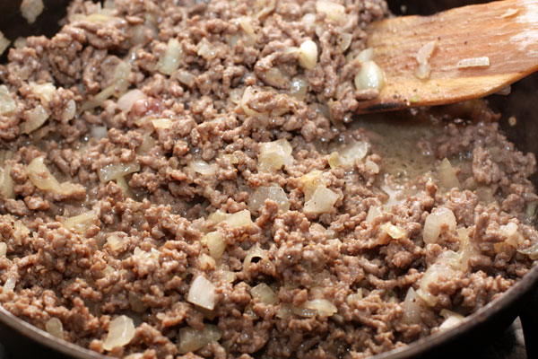 Добавьте фарш и продолжайте готовить, помешивая, на среднем огне до тех пор, пока фарш полностью не потеряет розовый оттенок. Посолите и поперчите.
