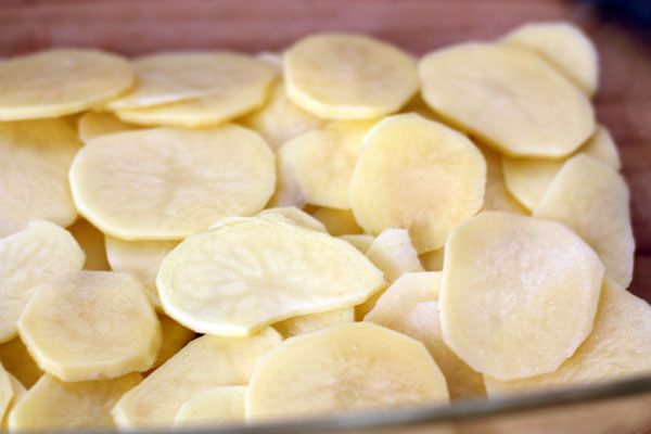 Форму для запекания смажьте маслом и выложите ломтиками картофеля внахлест (должна уйти примерно треть всего объема картошки).