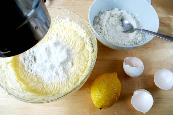 Затем надо будет добавить цедру лимона, коньяк и просеянную муку.  Муку добавляем не всю сразу а частями, тщательно вымешивая на минимальной скорости