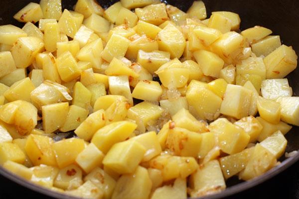 Добавьте очищенную и нарезанную кубиками картошку, перемешайте и готовьте 15 минут, периодически помешивая. Посолите и поперчите.