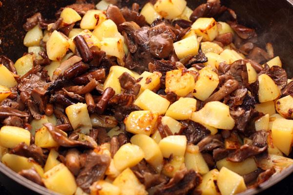 Отваренные грибы положите в сковороду к картошке.