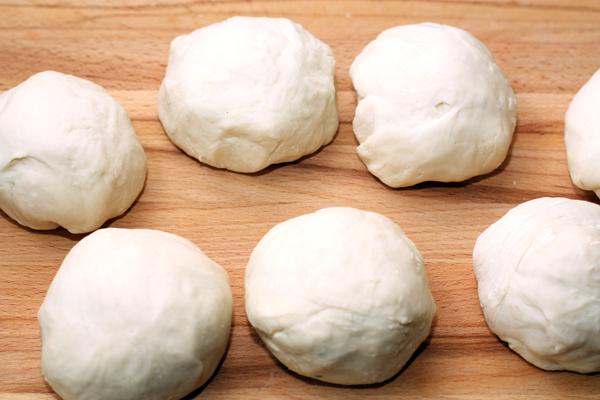 Из теста сделайте 6-8 одинаковых шариков (примерно по 130-140 г. Используйте муку для подсыпки, при необходимости. Опять накройте шарики полотенцем и оставьте на 10 минут.