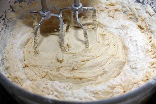 Просейте в миску муку с разрыхлителем, добавьте ванильный сахар и взбивайте дальше.