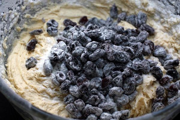Изюм вымойте, замочите в кипятке на 2-3 минуты, затем обсушите, обваляйте в муке и добавьте в тесто. Перемешайте.