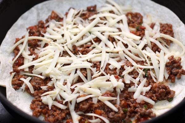 На сухую разогретую сковороду положите тортилью, посыпьте ее тертым сыром, затем выложите мясную начинку и снова покройте слоем сыра.