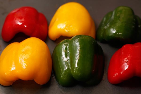 Для начинки сначала нужно запечь перец. Для этого очищенный от семян и разрезанный на половинки перец, разложите на противне, смазанном оливковым маслом, кожицей вверх. Смажьте маслом кожицу и поставьте под гриль на 10-15 минут.