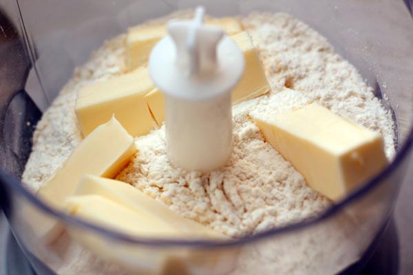 Для теста нужно просеять муку, добавить очень холодное масло и быстро порубить все в мелкую крошку. Очень удобно это делать двумя ножами или блендером.