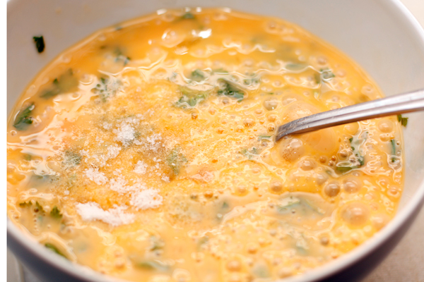 В отдельной миске слегка взбейте вилкой яйца с мелко нарезанной зеленью и солью.