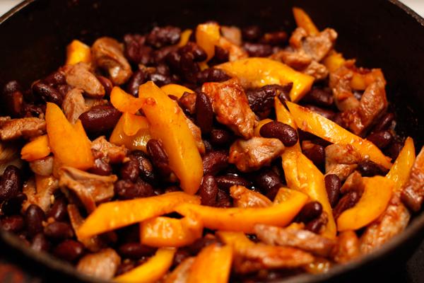 Сладкий перец нарежьте полосками и тоже положите в сковороду. Обжарьте все вместе 2-3 минуты.