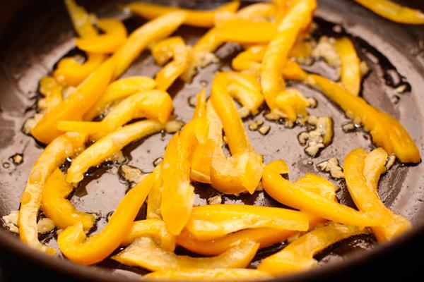 Следом добавьте нарезанный полосками перец и готовьте на довольно большом огне 2-3 минуты.