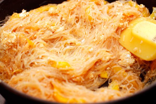 Перемешайте, затем сдвиньте лапшу на одну половину сковороды, а на другой быстро обжарьте взболтанные яйца. <br> Когда яйца схватятся, смешайте их с лапшой.