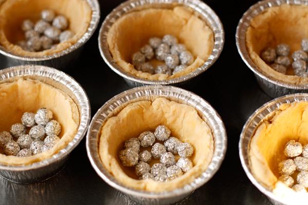 Насыпьте в формы шарики для выпечки (или фасоль) и пеките в разогретой до 200 градусов духовке 15 минут, затем уберите груз и пеките еще 10-15 минут до светло-золотистого цвета.