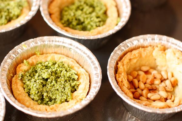 В испеченные тарталетки насыпьте по чайной ложке орешков, затем наполните их сырной смесью.