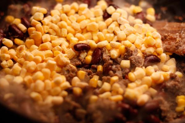 Положите в сковороду с фаршем вареную фасоль (или консервированную в собственном соку, для быстроты) и кукурузу, перемешайте и жарьте 2-3 минуты.
