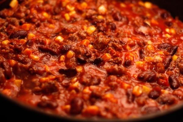 Добавьте томатное пюре, специи, перемешайте и посолите. Готовьте еще 5 минут, чтобы жидкость немного испарилась.