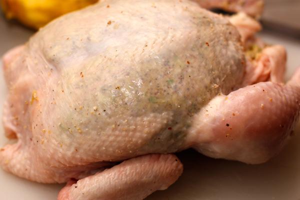 Аккуратно приподнимите кожу на грудке и образовавшийся карман наполните фаршем. Довольно плотно, но так, чтобы не порвать кожу.<br>  Внутрь курицы положите половинку того лимона, с которого снимали цедру и свяжите ноги вместе.