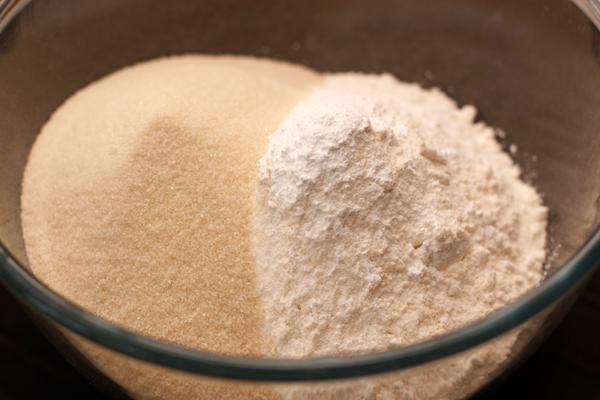 В большую миску просейте муку с разрыхлителем, добавьте измельченный миндаль и сахар.