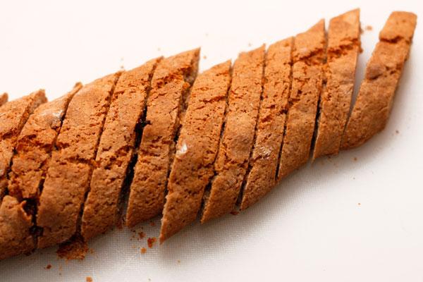 Поставьте батончики в горячую (180 градусов) духовку и запекайте около 30 минут. Готовность можно проверить деревянной зубочисткой — она должна выйти сухой.  Дайте батончикам немного остыть и нарежьте наискосок острым ножом на ломтики толщиной около 1 см.