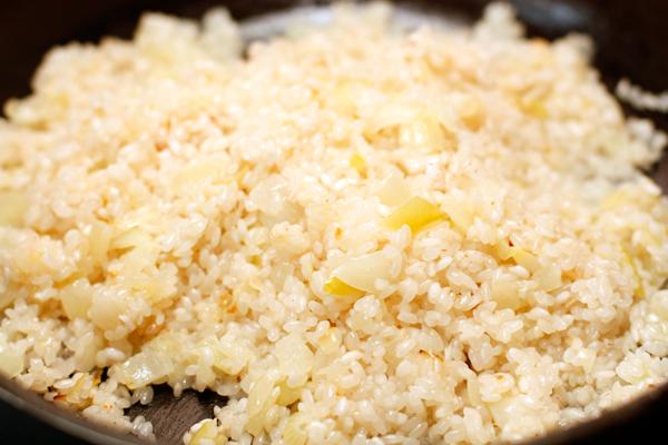 Мелко нарезанный лук спассеруйте на оливковом масле, добавьте рис и готовьте до прозрачности 2-3 минуты.