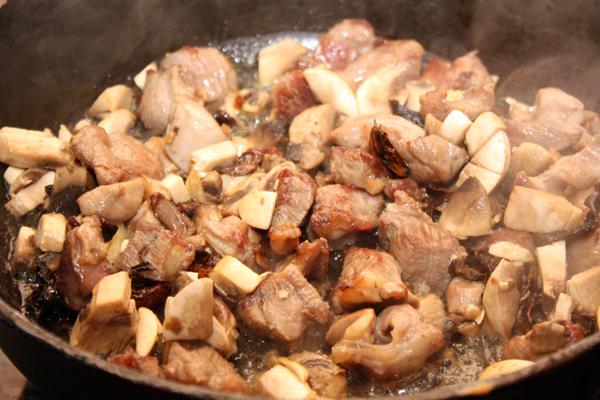Когда мясо станет светло-коричневым, добавить в сковороду белые грибы вместе с жидкостью и нарезанные шампиньоны. Убавить огонь, влить вино и готовить без крышки 10-15 минут.