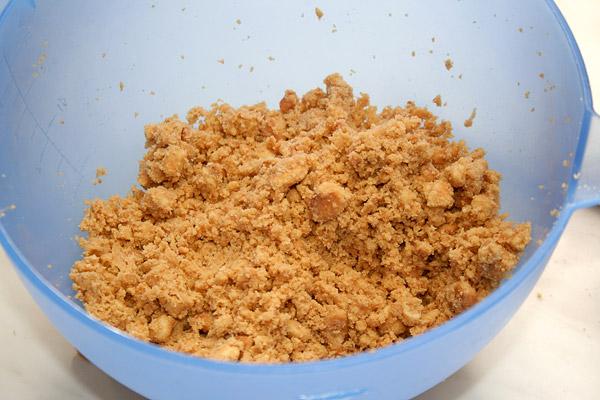 В печенье добавляем мелко порубленное и сильно охлаждённое сливочное масло и тщательно перемешиваем.