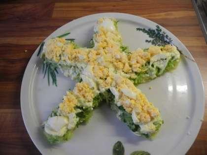 На огурцы выложить слой тертых яиц, посолить и промазать майонезом