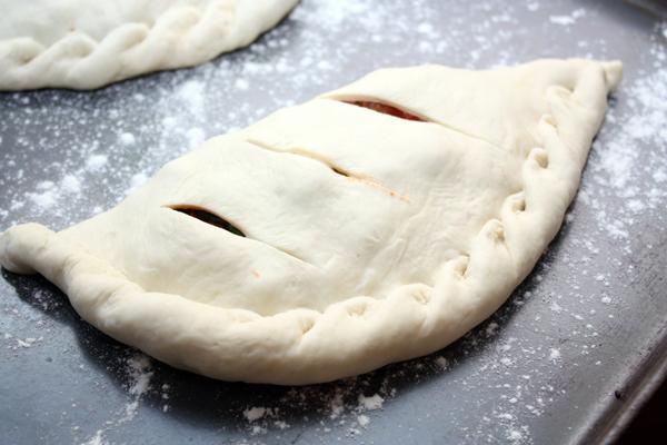 Положите пиццу на противень, сделайте несколько надрезов, чтобы выходил пар и лишняя жидкость, сбрызните маслом.