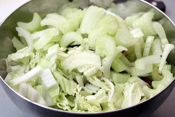 Добавьте нарезанный китайский салат и сельдерей. У сельдерея лучше удалить волокна, если он не слишком молодой.