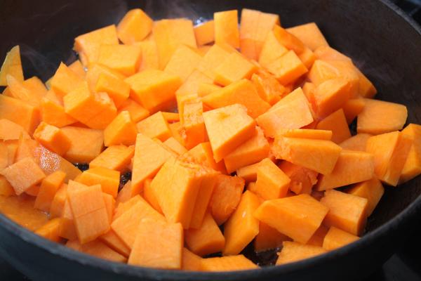 Очистите тыкву (возьмите около 700 грамм неочищенной тыквы), нарежьте кубиками и обжарьте на горячей сковороде 5-7 минут. Затем уменьшите огонь и готовьте еще минут 5.