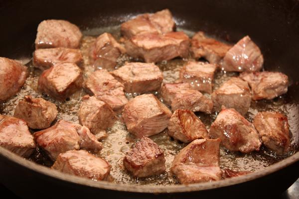 Кусочки мяса обжарьте, чтобы образовалась корочка. Для этого кладите мясо только на очень горячую сковороду и небольшими порциями, чтобы оно лежало свободно.