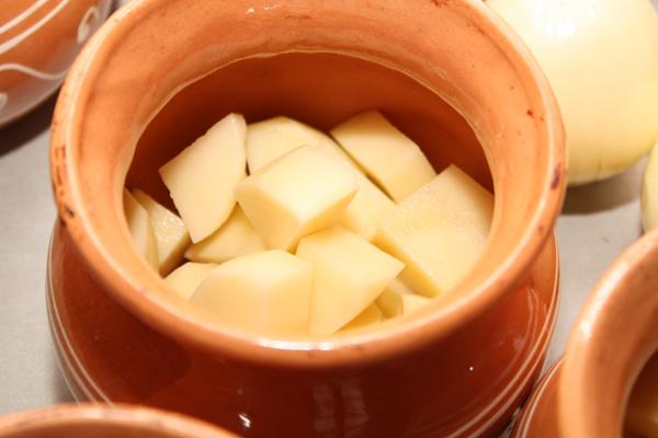 В каждый горшочек положите кусочки картофеля примерно на треть высоты.
