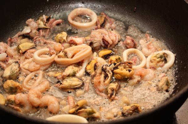 Выложить в сковороду морепродукты. Если вы используете замороженные (как я в данном случае), то их лучше заранее разморозить и слить жидкость.  Готовить буквально 1 минуту.