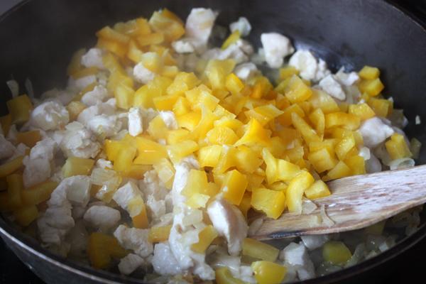 Когда курица побелеет, кладем в сковороду кубики желтого сладкого перца.