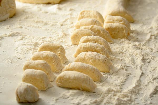 Присыпать стол мукой, выложить тесто, разделить на 3−4 куска. Каждый кусок раскатать в тонкую колбаску и нарезать маленькими кусочками.