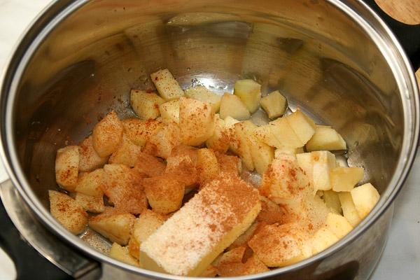 Посыпать сахаром, порошком корицы, добавить сливочное масло и поставить на медленный огонь. Периодически помешивая довести до кипения.