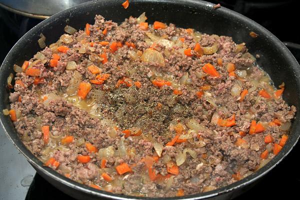 Добавить к овощам приготовленный фарш и обжарить все вместе в течение 10 минут. Добавить по вкусу соль, молотый перец, тимьян и базилик.