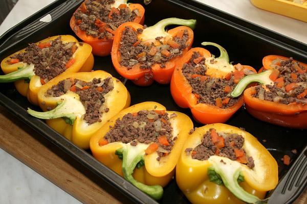 Нафаршировать перец мясом. Разогреть духовку до 200 °С. Аккуратно сложить фаршированный перец в форму для запекания и поставить на 20 минут в духовку.