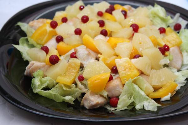 На большую тарелку выкладываем слоями листья салата, курицу, ананас и перец, поливаем заправкой и украшаем ягодами брусники.