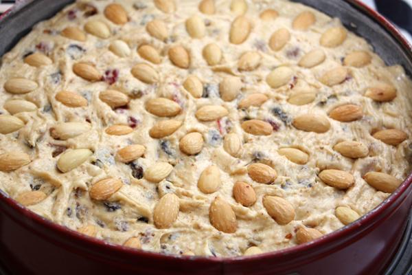 Выложить тесто в форму, смазанную маслом и обсыпанную мукой. Разровнять и украсить очищенным миндалем.