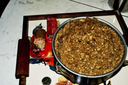 Смешиваем измельченное печенье и орехи и добавляем в смесь растопленное сливочное масло, все тщательно перемешиваем