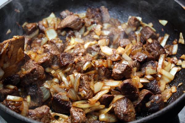 К обжаренному мясо добавить нарезанный соломкой репчатый лук и готовить все вместе, помешивая еще 2-3 минуты.