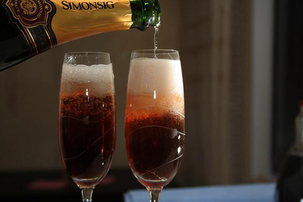 И сверху аккуратно долить до почти полного бокала шампанское. Наливать нужно аккуратно, чтобы гранатовый сок остался внизу, а шампанское было верхним слоем. И добавить в бокал 7−10 зерен граната.