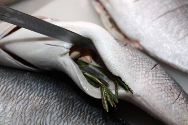 Рыбу нужно тщательно почистить и положить внутрь по веточке розмарина, и по паре неочищенных зубчиков чеснока. У меня было 3 шт. примерно по 400 грамм.