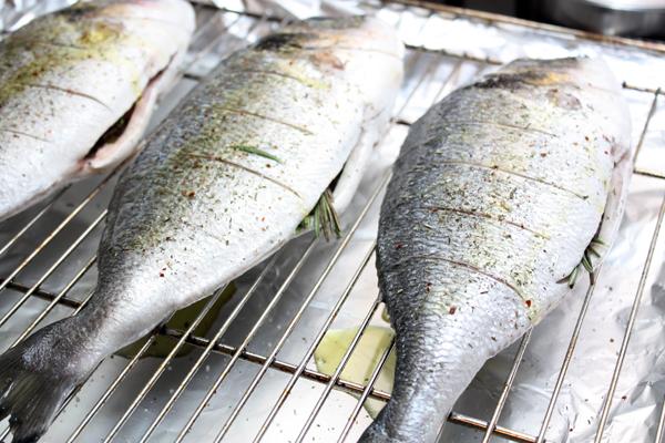 На каждой рыбине сделать неглубокие надрезы, посолить, поперчить, сбрызнуть оливковым маслом.