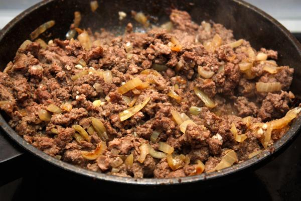 Лук нарезать и спассеровать до золотистого цвета в растительном масле, добавить в сковороду фарш и обжарить все вместе 5-10 минут, помешивая.