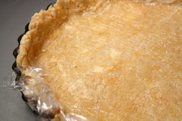 Холодное тесто раскатываем прямо на пищевой пленке с помощью посыпанной мукой скалки до толщины примерно 0,5 см и переворачиваем в форму для пирога.