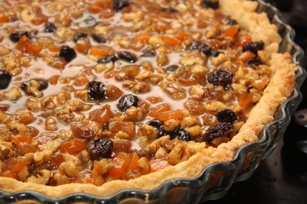 В готовую остуженную ириску добавить сухофрукты и нарезанные орехи, перемешать и вылить на испеченную основу, равномерно распределить.