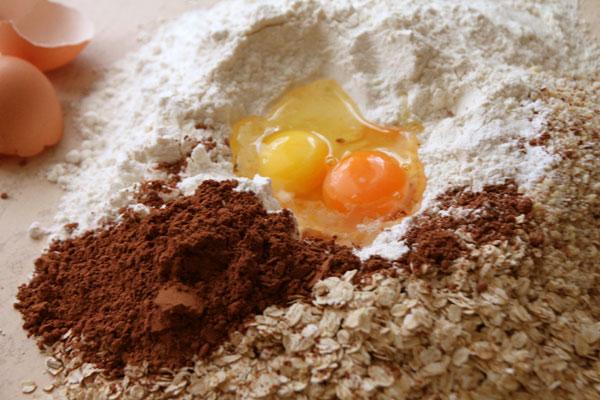 Пока остывает сироп начнём готовить тесто. На рабочую поверхность высыпьте горкой муку, тонкие овсяные хлопья, разрыхлитель, какао, сахар и порезанное хлопьями сливочное масло. В центре горки сделайте углубление и вылейте туда яйцо и желток. Теперь смешайте всё в однородную рассыпчатую смесь.