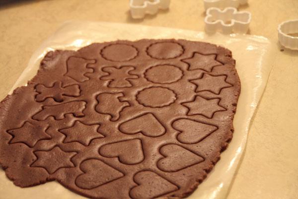 Раскатываем его на бумаге для выпечки и вырезаем фигурки с помощью формочек. Лишнее тесто убираем.